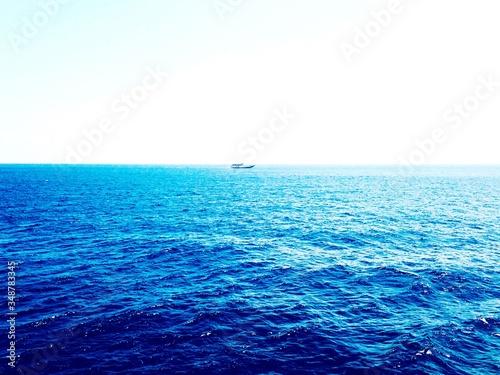 Cuadros en Lienzo Distant View Of Motorboat In Blue Sea Against Clear Sky