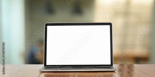Obraz Photo of white blank screen computer laptop putting on working desk over comfortable living room as background. - fototapety do salonu