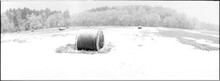 Panoramic Shot Of Hay Bales On Snowy Field During Winter