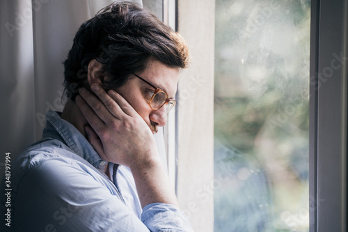 Portrait of one guy longing and looking through window Wallpaper Mural