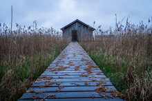 View Over A Wooden Footbridge To The Boathouse On Lake Ammersee In Germany