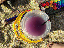 Directly Above View Of Bucket And Paint On Sand At Beach