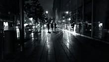 Women Walking Along The Street At Night