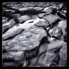 Frozen Brook Between Stones In Wintertime