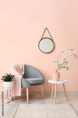 Obraz Interior of living room with stylish mirror and blooming tree branches - fototapety do salonu