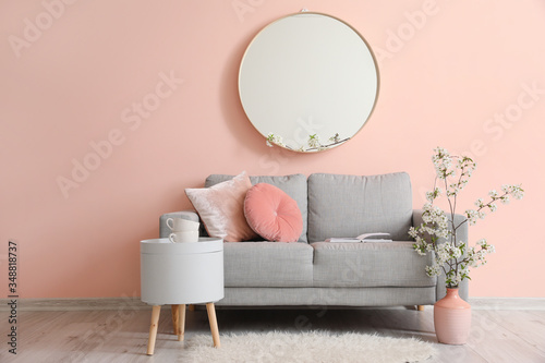 Fototapeta Interior of living room with stylish mirror and blooming tree branches obraz