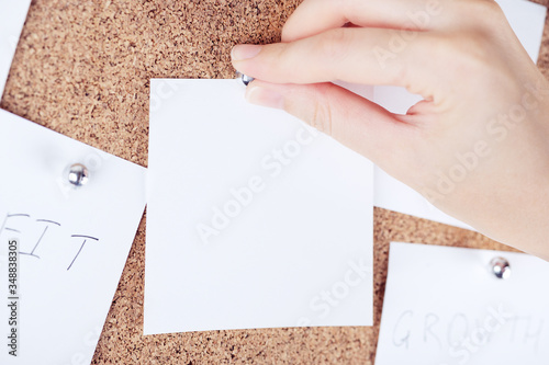 Photo Top view of person hand attaching reminder sticky note to cork board
