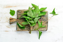 Fresh Green Nettles On A White Wooden Background. Healthy Herbs. Top View.
