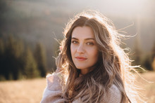 Portrait Of A Young Beautiful Girl With Long Hair In Autumn Mountains At Sunset.