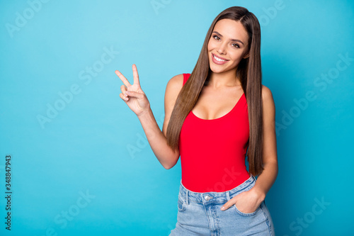 Fototapeta Portrait of candid pretty cute sweet lovely girl enjoy spring rest relax make v-sign wear good look tank-top isolated over blue color background obraz