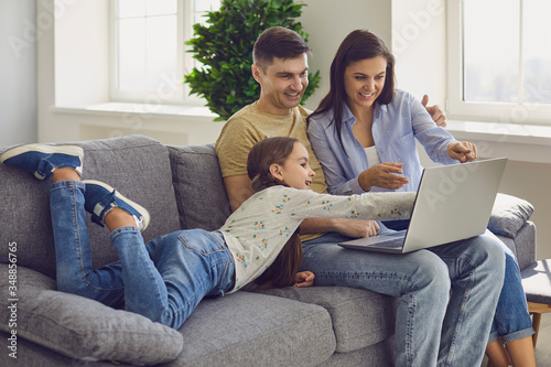 Family laptop online. Parents and a kid child look at a laptop at their leisure in a weekend at home.