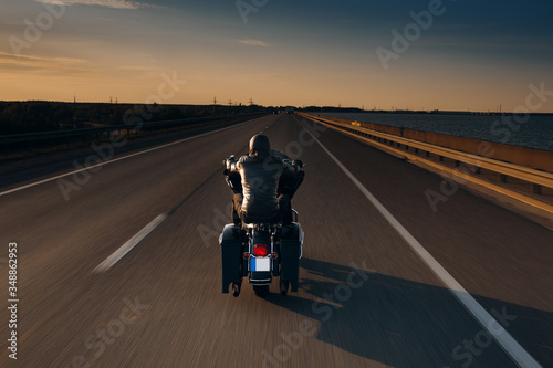 Photo Motorcycle driver riding alone on asphalt motorway