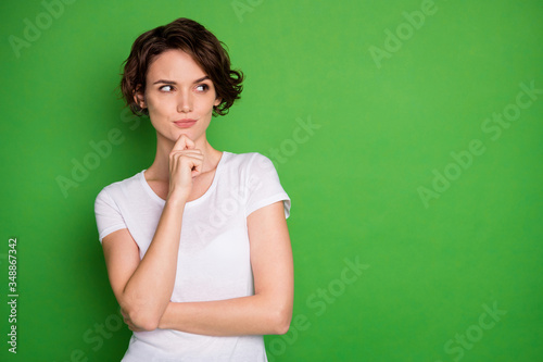 Fototapeta Photo of attractive lady short wavy hairdo look interested side empty space have creative idea crazy cunning eyes sly person wear casual white t-shirt isolated green color background obraz