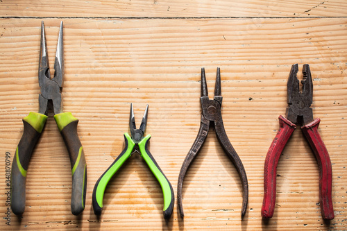 Obraz na plátne VARIOUS PLIERS LAYING ON A WOODEN TABLE