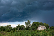 Heavy Rain Near An Old Abandoned House In A Distant Village. Green Nature