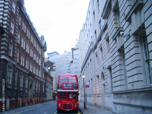Vászonkép Double-decker Bus On Street Amidst Buildings In City