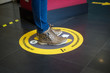 Closeup of feet of woman standing in the social distancing symbol on the floor in the train station  during the Covid-19 pandemic