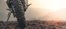 Part Of A Motocross Wheel On A Mound, With Sunrise.copyspace For Your Individual Text