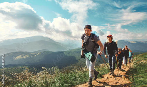 Company of friends travelers walking on the mountain hill with grass field, hiking in mountains, enjoying beautiful scenery Fototapeta
