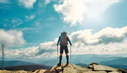 Fotografia Rear view man traveler hiking stand on top of mountain against beautiful cloudy sky, enjoying nature view, solo traveling