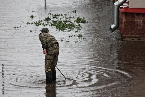 Obraz na plátne A service man in camouflage clothing searches for a manhole under water in a lar