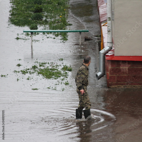 Vászonkép A man in camouflage clothing walks through a large puddle on the background of a