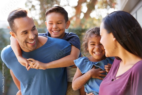 Smiling Hispanic Family With Parents Giving Children Piggyback Rides In Garden A Fototapet