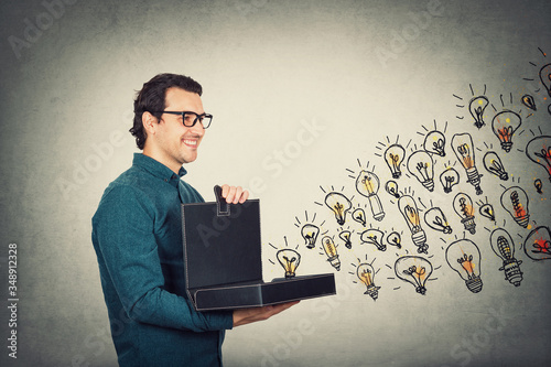 Businessman opens his briefcase filled with brilliant ideas as different lightbulbs comes out of the box Canvas Print