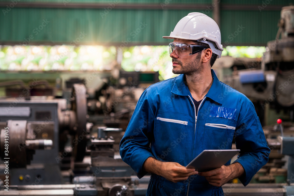 Fototapeta Engineers and skilled technicians are maintaining machinery. Professional technicians are holding a tablet to control work in industrial plants.