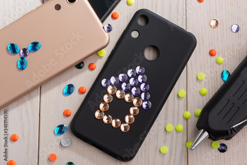 Photo Child attaching rhinestones onto phone cases with a glue gun