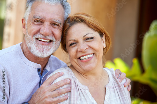 Portrait Of Smiling Senior Hispanic Couple Relaxing In Garden At Home Together Canvas Print