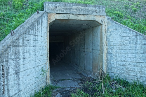 Slika na platnu the entrance to the old tunnel of gray concrete in the ground and green grass on
