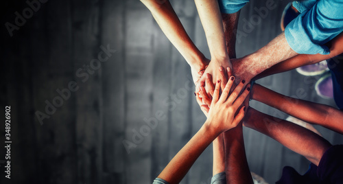 Fotografie, Tablou Close up top view of young business people putting their hands together