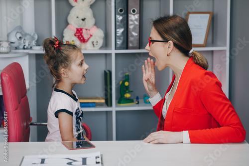 Photo Cute little girl at speech therapist's office