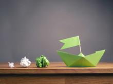 New Ideas Or Teamwork Concept With Crumpled Paper And A Green Paper Boat