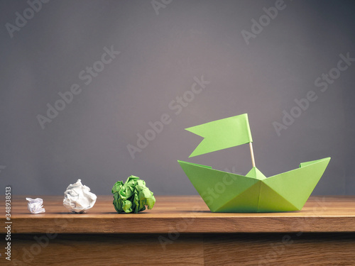 Obraz na płótnie New ideas or teamwork concept with crumpled paper and a green paper boat