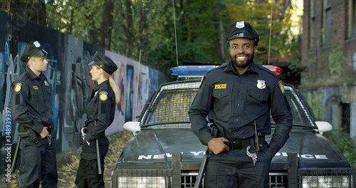 Fototapeta Happy and smiling African American police officer looking at camera