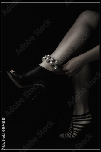 Low Section Of Woman Wearing Anklet Against Black Background Canvas Print