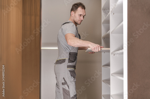 Fotografie, Tablou Constraction Male Assembling Cabinets In Closet.