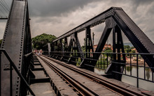Railroad Bridge Over River Against Cloudy Sky