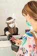 Leinwandbild Motiv cliente con abito a fiori e mascherina, paga con carta di credito alla cassa protetta da vetro in plexiglas con operatrice dotata di tutti i dispotici di protezione
