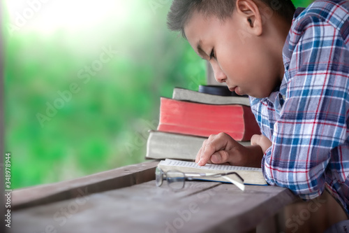 Obraz na plátne Boy holding and reading the Bible on wooden table, Christian concept