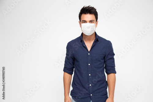 Stampa su Tela Young caucasian man wearing face mask to protect from COVID-19 and looking at ca