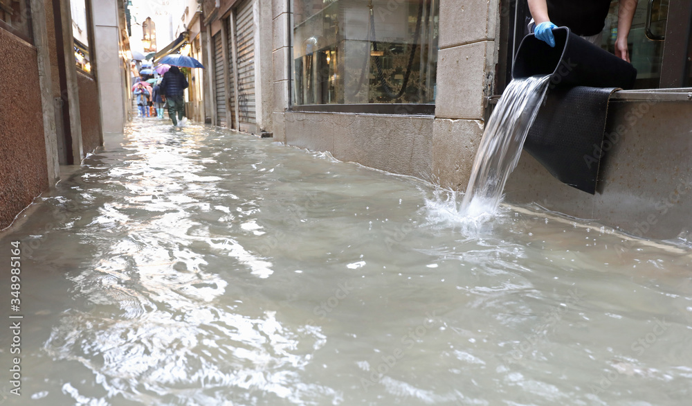 Fototapeta person emptying the interior of the shop flooded after the flood