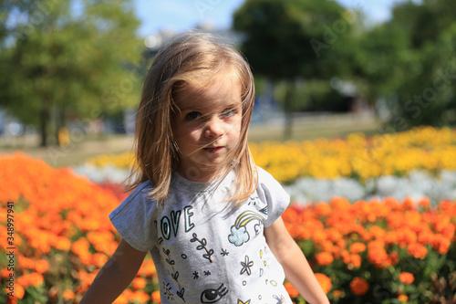 Fototapeta Mała dziewczynka na tle kwiatów obraz