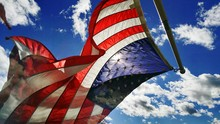 Low Angle View Of American Flag Waving Against Blue Sky