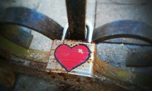 Close-up Of Rusty Padlock With Heart Shape On Railing