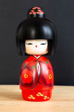 Kokeshi Doll In Red Kimono. Still-life Photo Taken On Studio Of A Japanese Traditional Doll.
