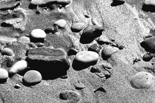 High Angle View Of Pebbles On Wet Sandy Beach
