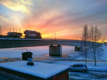 Bridge Over Frozen River Against Dramatic Sky During Sunset